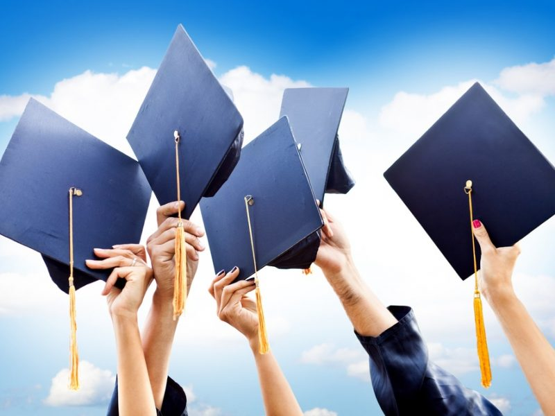 Unrecognizable group of people throwing graduations hats in the air
